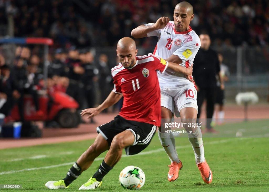 Tunisian forward Wahbi Khazri (R) vies for the ball against Libya's midfielder Ahmad Benali (L) during their World Cup 2018 qualifying football match at the Rades Olympic Stadium in the capital Tunis on November 11, 2017. /