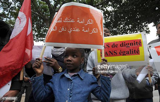 Tunisian girl holds up a placard during a demonstration against racism in the capital Tunis Tunisia on March 21 2014