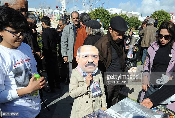 A Tunisian girl wears a mask of slain opposition leader Chokri Belaid during a gathering marking the first anniversary of his assassination on...