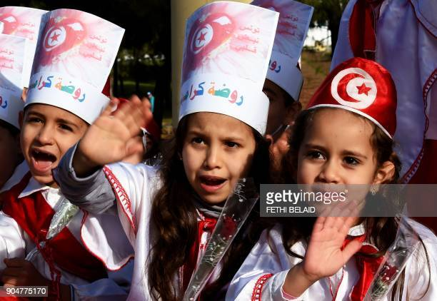 Tunisian girls wave in Ettadhamen city on January 14 2018 as Tunisians gather in the streets to mark seven years since the uprising that launched the...