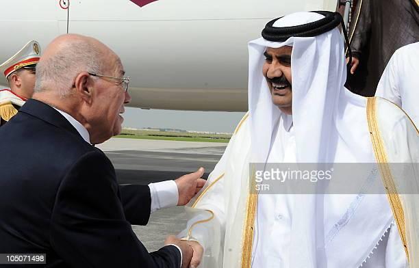 Tunisian government minister and Special Advisor to the president Abdelaziz ben Dhia shakes hands with Emir of Qatar Sheikh Hamad bin Khalifa...