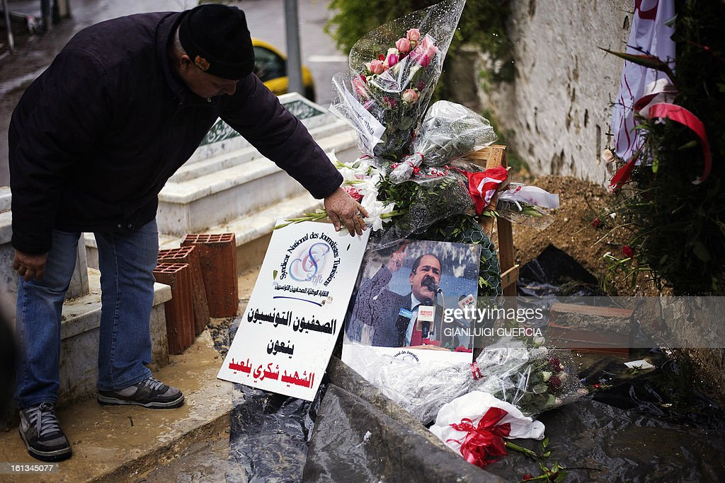 A Tunisian graveyard worker fixes the flowers placed on the grave of assassinated opposition leader Chokri Belaid at El-Jellaz cemetery in a suburb of Tunis on February 10, 2013. Prime Minister Hamadi Jebali's gamble on forming a new government in defiance of his own Islamist party after the assassination of opposition head Chokri Belaid left Tunisia in political limbo.
