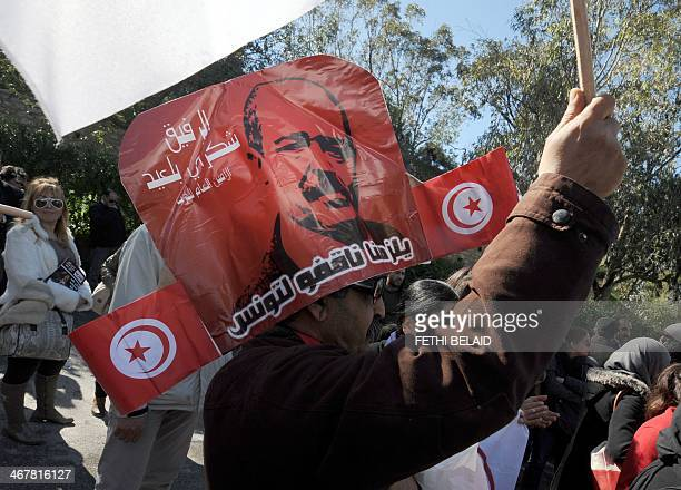 A Tunisian has a makeshift hat made of posters showing murdered opposition figure Chokri Belaid as people gather outside ElJellaz cemetery in a...