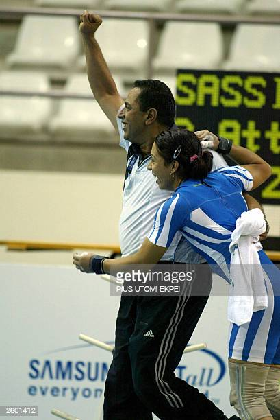 Tunisian Hayet Sassi celebrates with her coach after lifting 1225 kg clean and jerk 15 October 2003 to win gold and also set a new record at the...