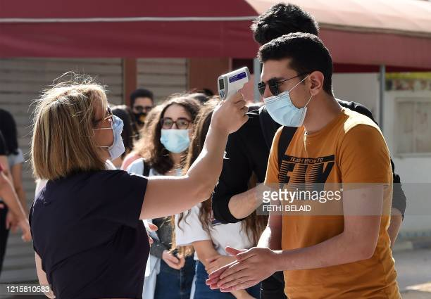 Tunisian highschool students have their temperatures checked at the courtyard of a school in Tunisia's capital Tunis on May 28, 2020 after...