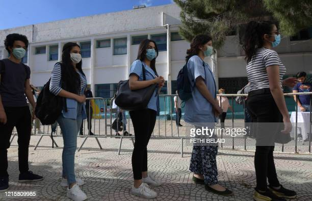 Tunisian highschool students wearing face masks stand in line at the courtyard of a school in Tunisia's capital Tunis on May 28, 2020 after...