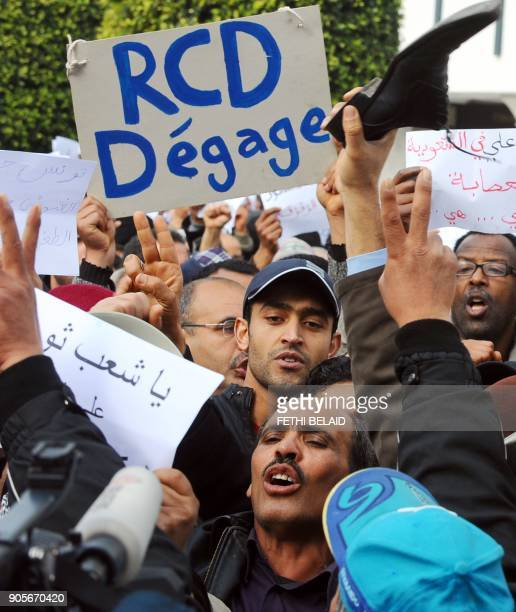 A Tunisian holds a cardboard reading 'RCD get out' as demonstrators shout slogans during a protest in Tunis on January 19 2011 Hundreds of people...