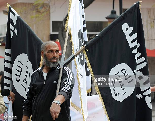 A Tunisian Islamist holding AlQaedaaffiliated flags attends a demonstration in Tunis on April 9 2013 to celebrate Martyrs' Day marking the deadly...