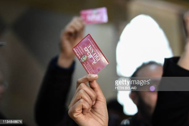 Tunisian journalists hold the press card during a protest at the Assembly of the Representatives of the People in Tunis on April 4 2019 Prime...