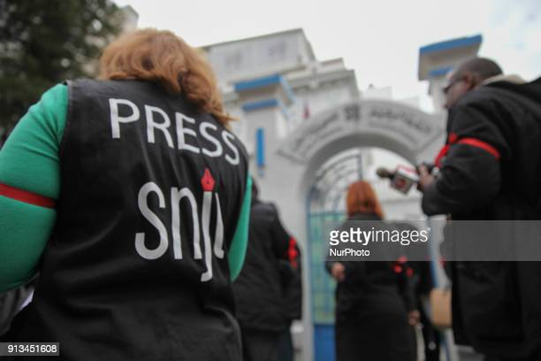 Tunisian journalists wear red ribbons around their arms during a demonstration held under the slogan Tunisian press in anger outside the headquarter...
