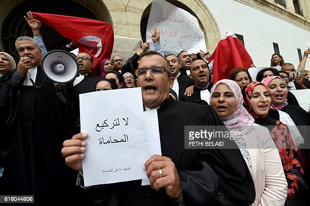 """Tunisian lawyer holds a placard reading in Arabic """"do not let lawyers go down on bended knees"""" during a protest outside Tunis law court against the..."""