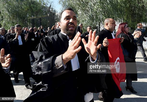 Tunisian lawyers shout slogans during a demonstration against a draft 2017 budget that would impose a public sector pay freeze on November 23, 2016...