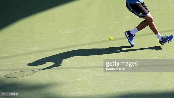 Tunisian Malek Jaziri's shadow is seen on the court as he hits a return to Russian Mikhail Youzhny during their ATP tennis match on the first round...