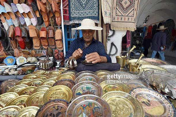A Tunisian man carves designs into a copper disk in the souk of Djerba on the Tunisian island on May 7 2015 AFP PHOTO / FETHI BELAID