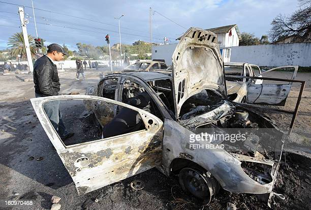 A Tunisian man inspects burnt cars that were set on fire by protesters following the funeral of assassinated opposition leader Chokri Belaid in Tunis...