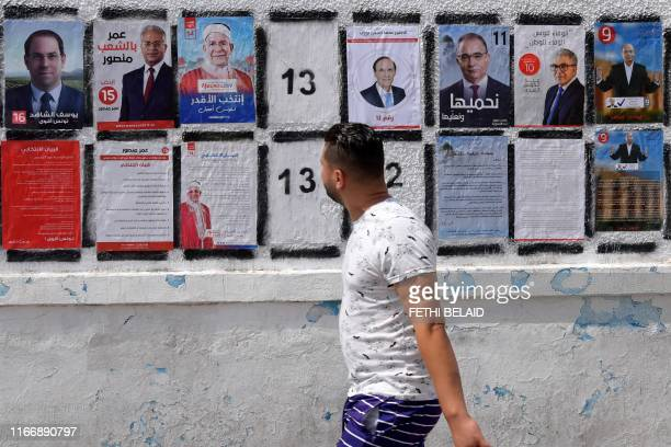 A Tunisian man walks in front of posters of presidential candidates in the capital Tunis on September 7 2019 Tunisia has long been seen as a pioneer...