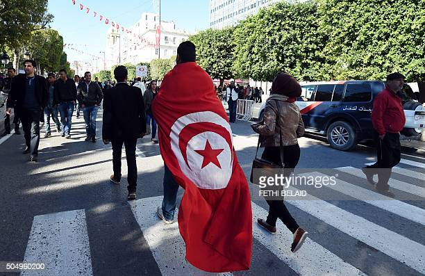 Tunisian man wears a cloth with a print of his national flag during a rally on January 14 2016 in the Habib Bourguiba Avenue in the capital Tunis to...