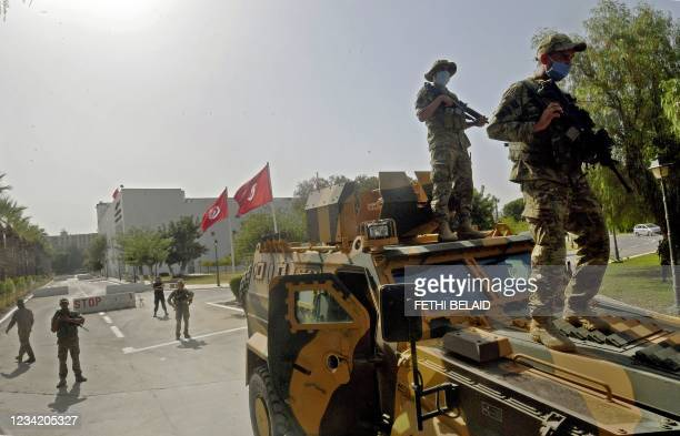 Tunisian military forces guard the area around the parliament building in the capital Tunis on July 26 following protests in reaction to a move by...
