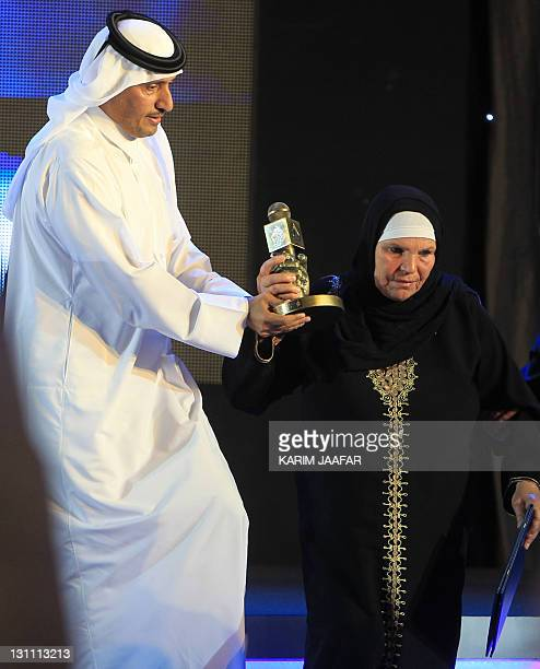 Tunisian mother of Mohamed Bouazizi holds an award as she stands with the new director-of the Qatar-based Al-Jazeera satellite channel Sheikh Ahmed...
