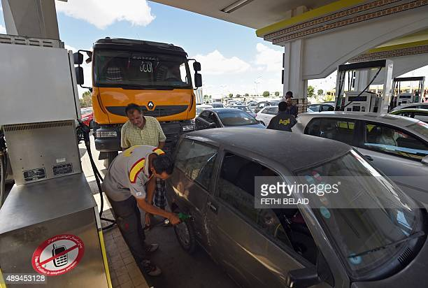 Tunisian motorists line up at the entrance of a gas station to refuel after the announcement of a strike by fuel transporters in Tunis on September...