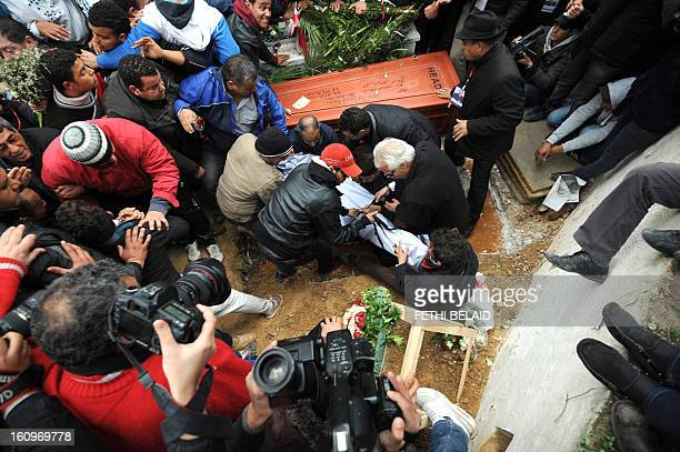 Tunisian mourners bury assassinated opposition leader Chokri Belaid at ElJellaz cemetery in a suburb of Tunis on February 8 2013 Tunisian police...