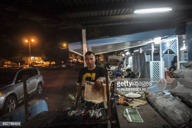 Tunisian Nageeb Zaatour 52 owner of Borol ole Mer restaurant grills fish for his customers in Franceville Gabon / AFP / KHALED DESOUKI