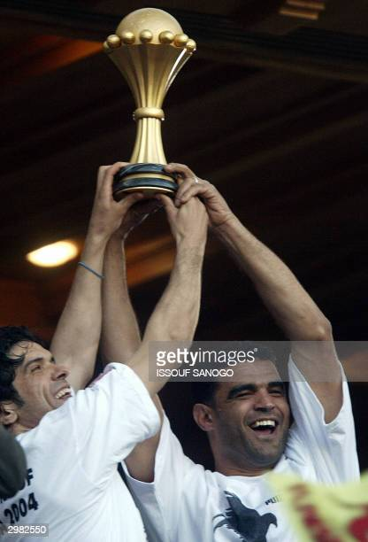 Tunisian national football team Riad Bouazizi and captain Khaled Badra celebrate with the trophy after defeating Morocco 21 in the final match of the...