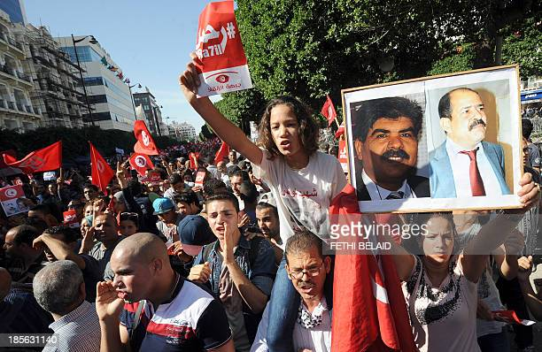 Tunisian opposition activists shout slogans as they hold portraits of assassinated Tunisian opposition figures Chokri Belaid and Mohamed Brahmi...
