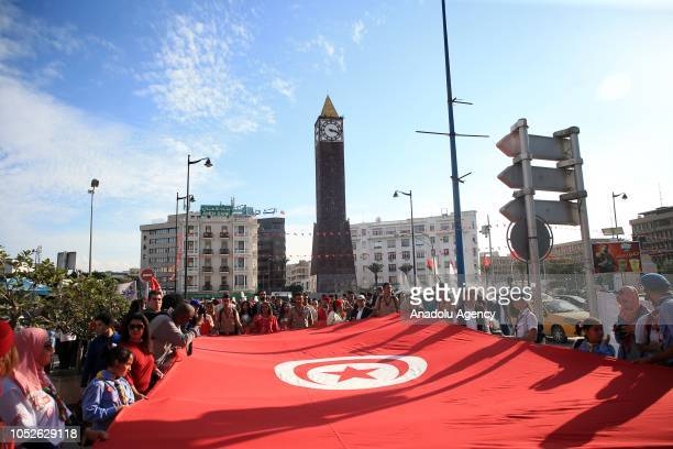Tunisian people hold national flags along Habib Bourguiba street during the celebration of 191st anniversary of creation of the Tunisian flag in...