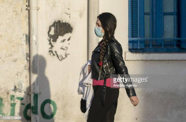 """Tunisian people walk at a street on the 10th anniversary of the """"Arab Spring"""" in Tunis, Tunisia on December 17, 2020. Ten years ago this week, a..."""