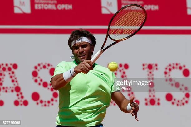 Tunisian player Malek Jaziri returns the ball to Portuguese tennis player Gastao Elias during their Millennium Estoril Open ATP Singles 1st round...
