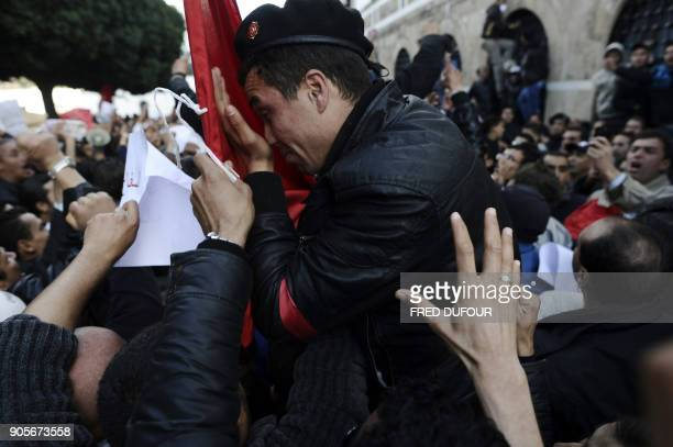 A Tunisian policeman cries next to a Tunisian national flag as demonstrators hold him up during a demonstration in Tunis on January 21 2011 Tunisia...