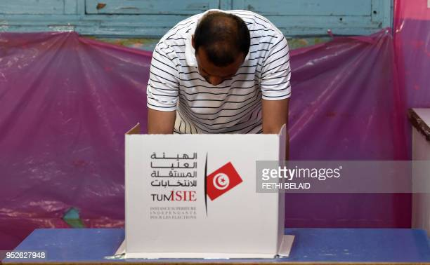 A Tunisian policeman dressed in civilian clothing ticks his ballot in the municipal elections at a polling station for the police and military in the...