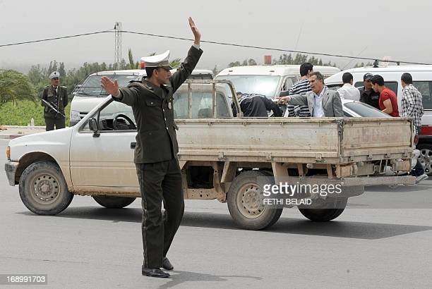 Tunisian policeman of a special unit stops a vehicle during controls on the highway leading to the Tunisian central city of Kairouan on May 18, 2013....