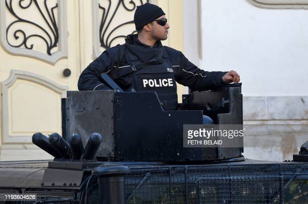 Tunisian policeman stands guard in central Tunis during a rally marking the ninth anniversary of the 2011 uprising on Habib Bourguiba Avenue on...
