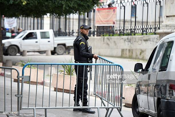 A Tunisian policeman stands guard in front of the court in Tunis on April 6 during the trial of nearly 80 people suspected of involvement in an...
