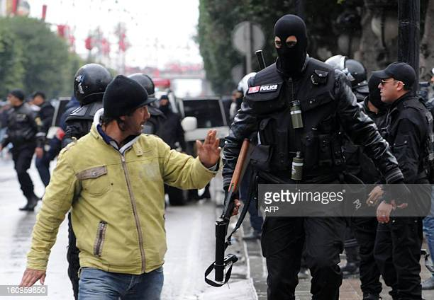 A Tunisian policemen gestures to a policeman as police disperse protesters during a demonstration following the funeral of assassinated opposition...