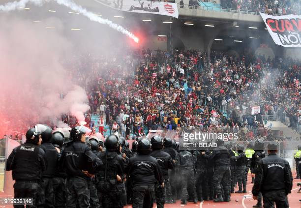 Tunisian policemen stand guard as fans throw flares during the Tunisia Ligue 1 football match derby between Esperance Sportive de Tunis and Club...
