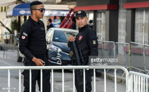 A Tunisian policemen stand guard outside a municipal elections polling station for the police and military in the capital Tunis on April 29 during a...