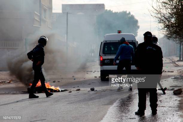 TOPSHOT Tunisian policemen stand in a street during a demonstration on December 25 2018 in the westcentral Tunisian city of Kasserine A Tunisian...