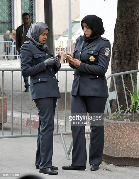 Tunisian policewomen check their mobile phones as they stand guard in front of the court in Tunis on April 6 during the trial of nearly 80 people...