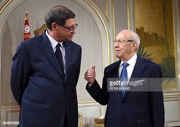 Tunisian President Beji Caid Essebsi speaks with Tunisian prime minister Habib Essid during an oath ceremony after the adoption of the Assembly of...