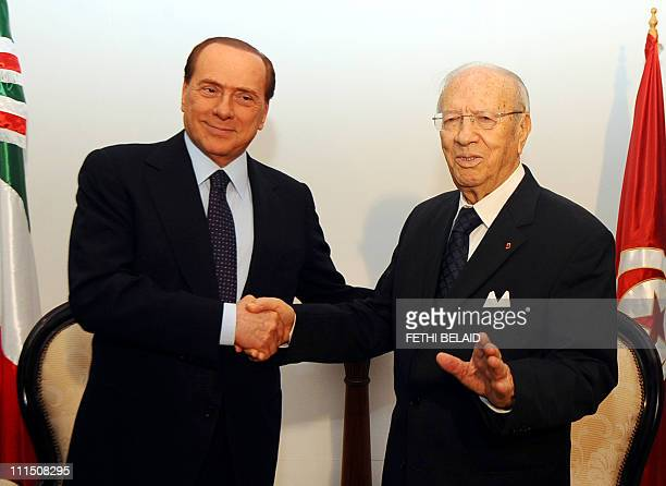 Tunisian prime minister Begi Caid Essebsi shakes hands with his Italian counterpart Silvio Berlusconi on April 4, 2011 upon his arrival at Tunis...