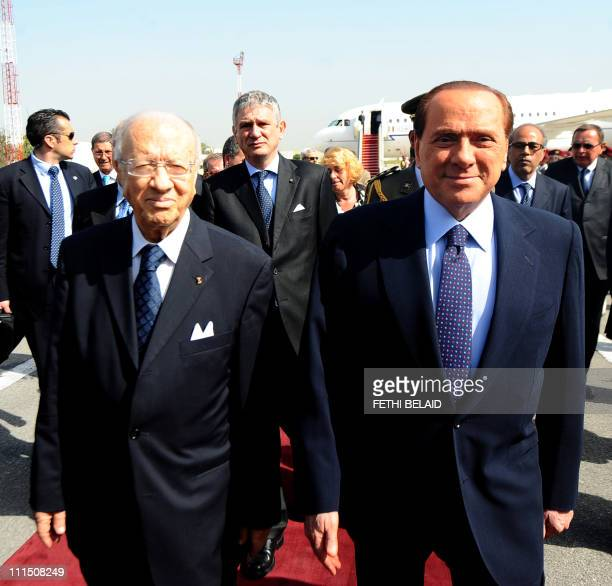 Tunisian prime minister Begi Caid Essebsi walks with his Italian counterpart Silvio Berlusconi on April 4, 2011 upon his arrival at Tunis airport. A...