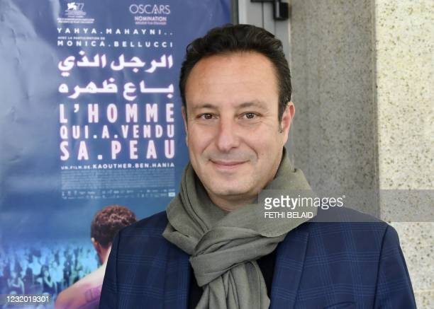 """Tunisian producer Mohamed Habib Attia poses in front of the poster of """"The man who sold his skin"""" upon his arrival to attend its first screening in..."""
