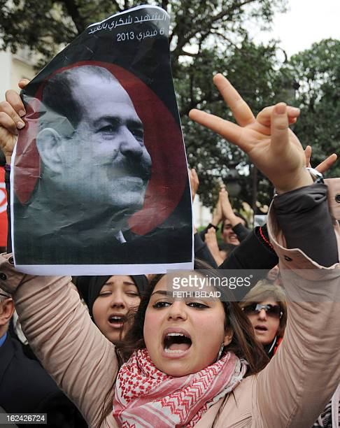 A Tunisian protester flashes the sign of victory holding a poster featuring killed opposition leader Chokri Belaid during a demonstration on February...