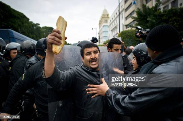 A Tunisian protester holding bread is pushed by riot policemen during a demonstration in Tunis on January 18 2011 Riot police fired tear gas and...