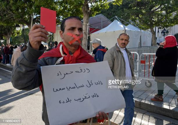 A Tunisian protester holds a red card as he holds a placard with a slogan criticising politicians in his country during a rally marking the ninth...