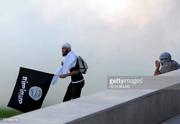 A Tunisian protester holds an AlQaeda affiliated flag amid the smoke coming from the tear gas fired by riot police during a protest against a film...
