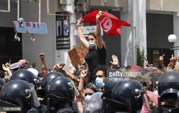 Tunisian protester lifts a national flag at an anti-government rally as security forces block off the road in front of the Parliament in the capital...